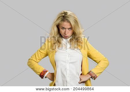 Portrait of dissatisfied young woman. Severe powerful frowning young woman holding hands on hips over gray background. Facial expression and body language.
