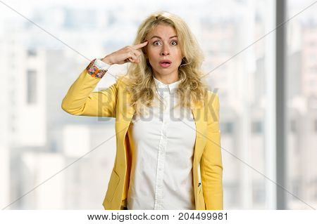 Young business woman forgetting something. Young european woman holding finger near temple with surprised face.