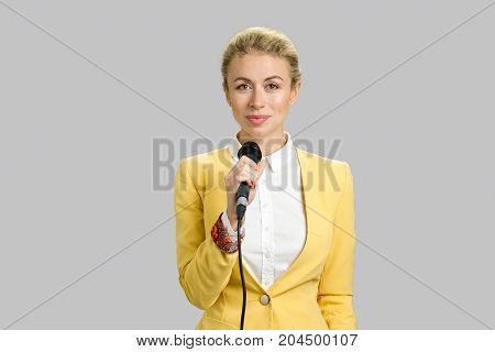 Young woman in formal wear with microphone. Young business woman public speaking isolated on grey background.