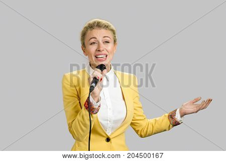 Business lady gesturing with microphone. Portrait of beautiful young european woman speaking on microphone on grey background.