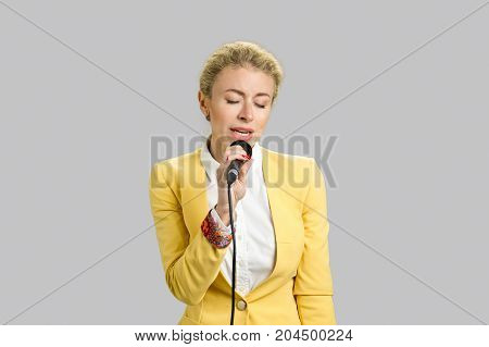 Beautiful young song performer, grey background. Charming lady in yellow jacket singing into microphone over grey background.