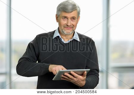 Mature man holding computer tablet. Man with grey hair using computer tablet and looking away. Senior man with digital tablet close up on blurred background.