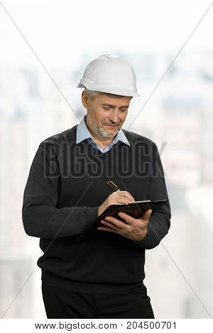 Mature foreman writing on clipboard. Senior manual worker with clipboard isolated on white background.