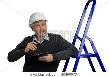Mature foreman looking upwards. Elderly engineer with clipboard leaning on ladder, white background.