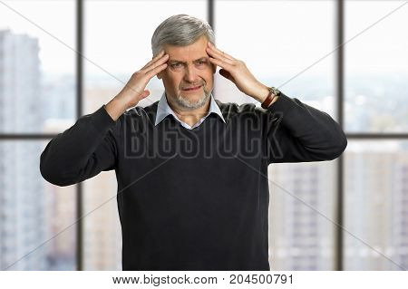 Mature man have strong headache. Frustrated senior man touching his head with fingers on office window background. Thinking about financial problems.