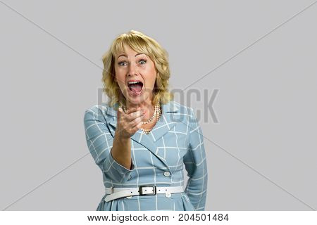 Mature woman laughing on grey background. Adult lady laughing with wide open mouth and pointing on someone index finger.