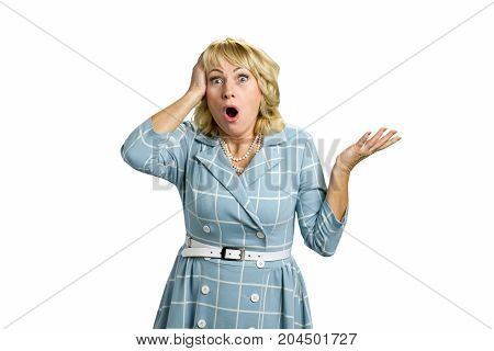 Elegant mature lady looking shocked. Surprised white-skin blonde with open mouth and hand on head, white background. Middle aged lady looking shocked.