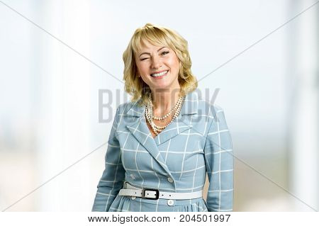 Beautiful twinkling mature woman. Portrait of smiling and positive white-skin woman in dress.