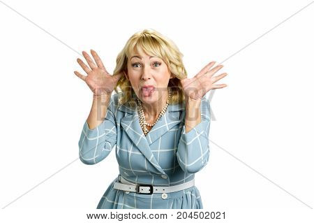 Adult woman making grimace. Mature woman showing her tongue and making a face while standing on white background.