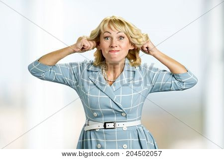 Mature woman making funny face. Adult woman making grimace stretching ears.