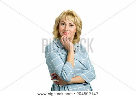 Portrait of attractive mature blonde. Middle aged woman holding hand on chin and looking at camera while standing on white background.