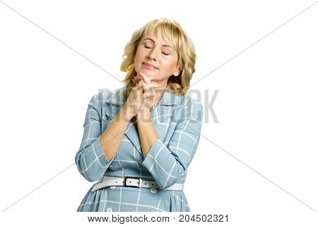 Relaxing mature woman on white background. Adult woman with clasping hands under chin and closed eyes isolated on white background.