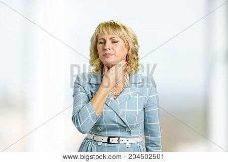 Mature woman having sore throat. Beautiful white-skin woman suffering from sore throat.