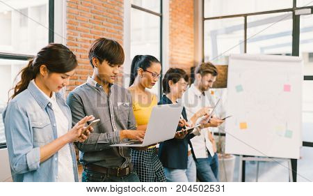 Multiethnic diverse group of happy young adult using information technology gadget devices together. Modern lifestyle culture casual business creative people education social media network concept