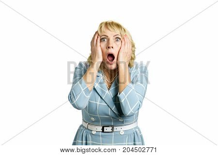 Portrait of woman in great shock. Mature woman with widely open mouth and eyes holding hand on head and looking shocked. Portrait of stunned white-skin woman on white background.