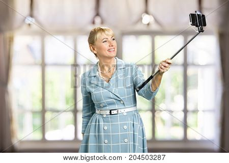 Smiling woman taking selfie with monopod. Attractive mature woman taking selfie with monopod on blurred background. Happy white-skin woman with monopod.
