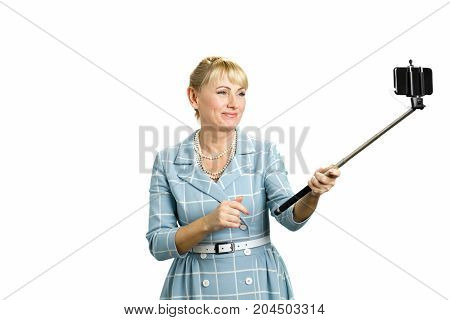Beautiful mature lady taking self portrait. Attractive middle aged woman taking selfie with selfie stick standing on white background.