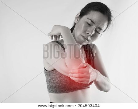 Young Asian woman in workout cloth holding hand and having Wrist Pain on isolated background red dot focus concept of health care.