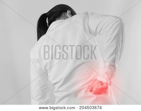 Young Asian woman in workout cloth holding hand and having Shoulder pain with red focus dot on isolated background. concept of health care view from rear people.