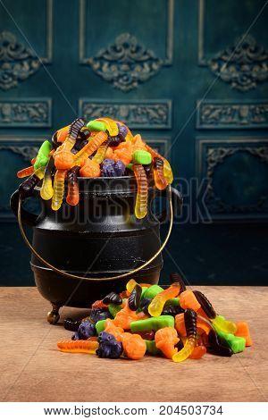 cauldron of gummy halloween candy on wood table