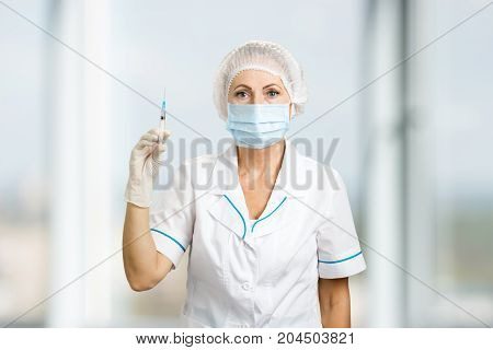 Portrait of nurse with syringe, front view. Close up of female mature doctor holding syringe with injection on blurred background.