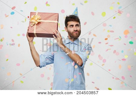 Bearded Young Man Recieves Wrapped Present From Friends On Birthday, Tries To Guess What It Is, Look