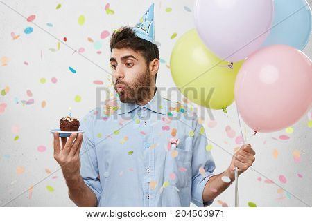 Festive Man In Party Hat And Formal Shirt, Celebrates Daughter`s Birthday, Bakes Little Cake, Holds