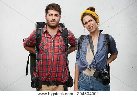 Distressed Female And Male Tourists Carry Heavy Luggage, Have Backache, Look Tiresome As Overcome Lo