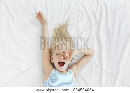 Top View Of Cute Blonde Little Girl Stretching In White Bed, Yawning And Rubbing Her Eyes, Awaking E