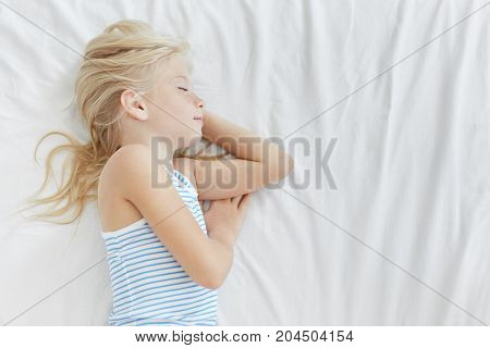Profile Portrait Of Cute 7-year Old Baby Girl With Light Hair Sleeping Comfortably In Her Bed, Havin