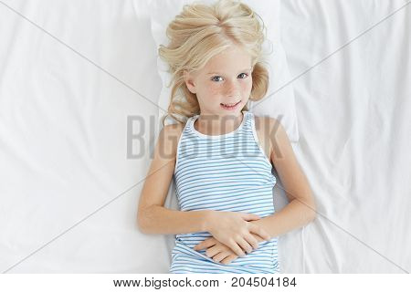 Top View Of Charming Little Blonde Girl With Cute Freckles All Over Her Face Lying On Pillow In Her