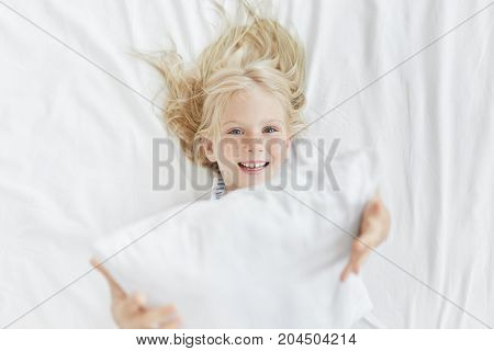 Funny Small Freckled Girl With Blue Eyes Plays In Bed With White Pillow, Smiles Broadly, Has Content