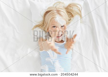 Lovely Charming 5-year Old Caucasian Girl With Blonde Hair And Freckled Face Lying On White Bedcloth