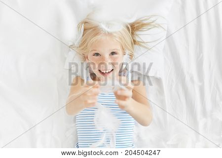 Portrait Of Playful Charming Freckled Little Baby Child Plays With Feather In Bed, Has Positive Expr