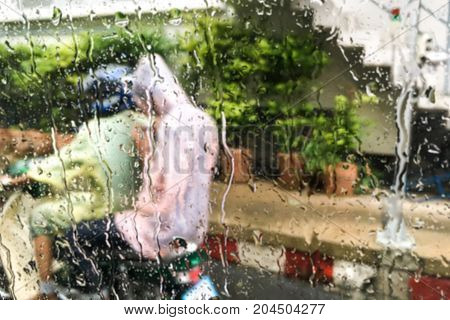 Blurred water drops on front mirror car and people wearing rain color clothes (rain suit) riding a motorbike (motorcycle) background- rainy day & abstract concept.