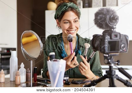 Candid Shot Of Beautiful Young Female Cosmetologist Tests New Kind Of Powder Brushes, Films Process