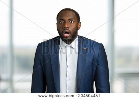 Afro american businessman surprised. Young black CEO manager opened mouth with astonishment. Astonished black man on blurred background.