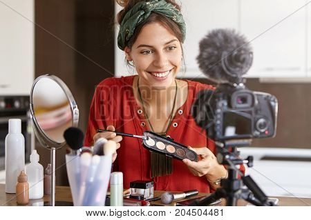 Indoor Shot Of Glad Woman Sits At Home, Uses Cosmetic Products For Making Video Diary, Looks At Came