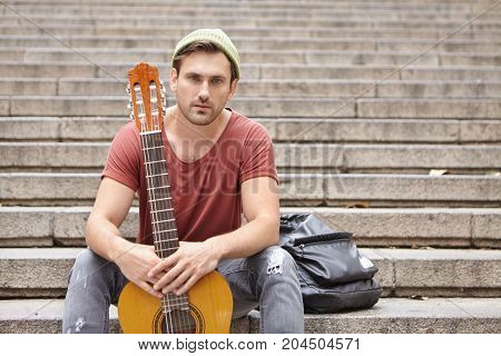 Music Is My Life. Confident Young Street Musician With Appealing Appearence, Wears Trendy Hat, Jeans