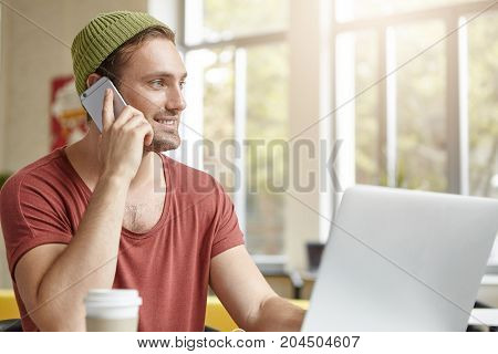 Indoor Shot Of Stylish Hipster Guy With Beard, Wears Hat And T-shirt, Calls His Friend Over Smart Ph
