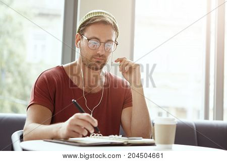 Handsome Unshaven Successful Businessman Wears Trendy Clothes, Takes Notes, Makes List Of Things To