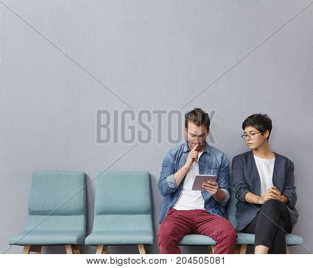 Two Stylish Male And Female Students Discuss Material Together, Sits On Chair Near Cabinet, Wait For