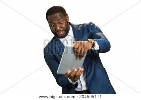 Emotional businessman plays computer game. Enthusiastic young manager with emotional interest holds computer tablet. Manager plays on computer tablet.