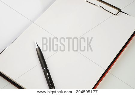 Paper Clipboard With A Blank Sheet Of Paper And Black Pen