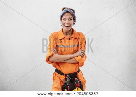 Horizontal Shot Of Beautiful Excited Young Woman Mechanic Opening Mouth And Keeping Arms Folded, Exp