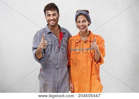 Two Service Workers Show Ok Sign, Smile Happily, Finish Their Work In Advance. Dirty Man Wears Unifo