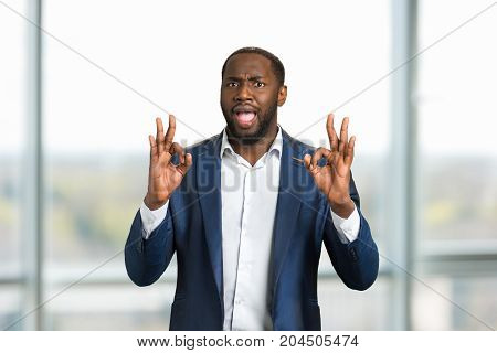 Black businessman gesturing OK. Young man in formal wear showing everything is allright with two hands.