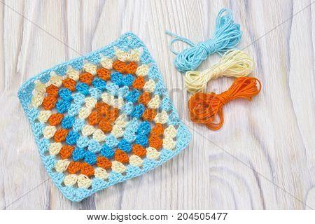 Crochet handmade granny square yarn balls. The beginning of bright plaid blanket. Colorful original knitted handmade work. Homemade creative crochet pattern. Crochet stitches. Rustic background