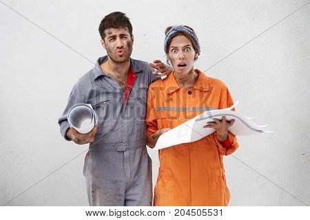 Displeased Female And Male Construction Workers, Hold Blueprint, Have Untidy Faces, Look With Discon