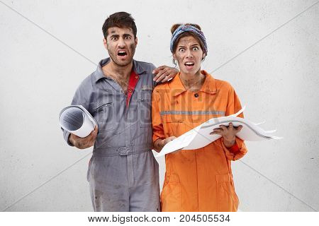 Portait Of Astonished Nervous Female And Male Maintenance Workers Or Carpenters Look With Unhappy Ex